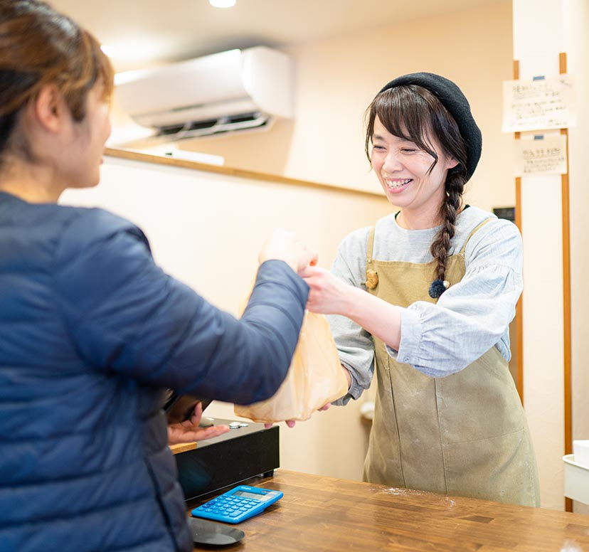 パン屋になった、笑顔が増えた。パンをお客様に渡す